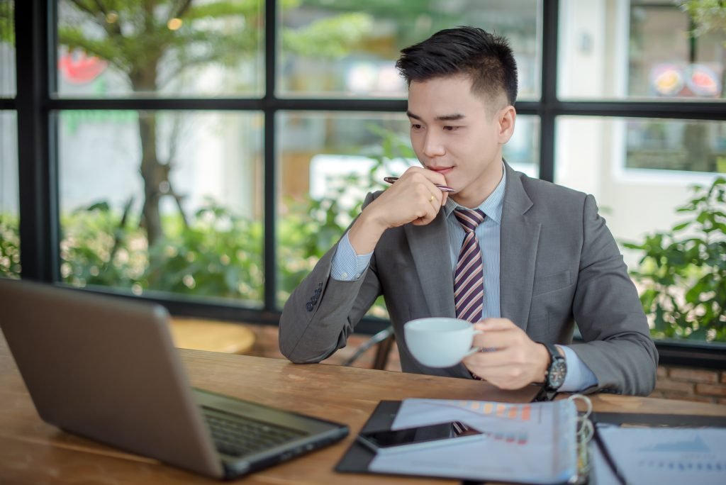 Man looking at laptop while holding his coffee